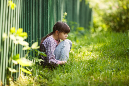 child alone: Little sad girl sitting on the grass Stock Photo