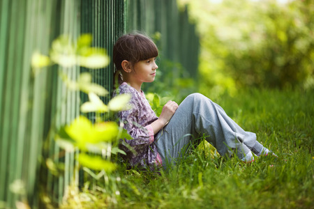 blessedness: Happy little girl sitting on the grass