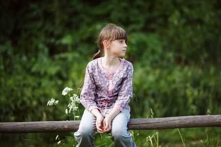blessedness: Beautiful little girl sitting on a wooden fence