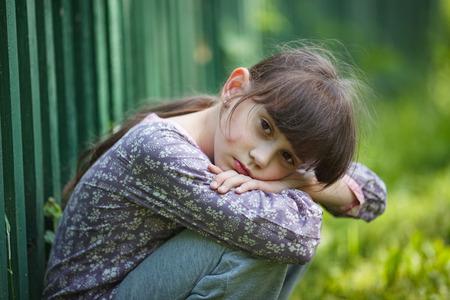 renunciation: Sad little girl sitting alone on the nature