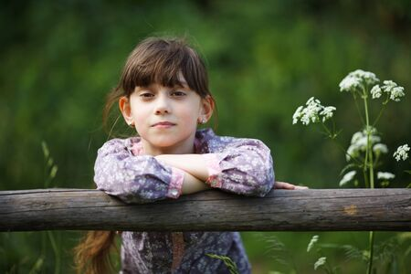 pacification: Beautiful little girl among the wildflowers in summer Stock Photo