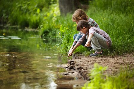 blessedness: Boy with a girl sitting near the water Stock Photo