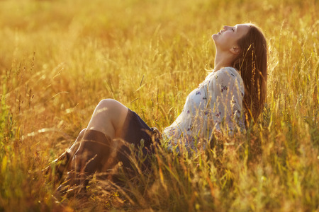 blessedness: Happy young woman sitting in the grass
