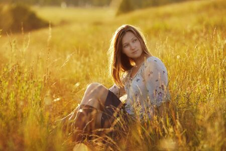 luxuriate: Beautiful young woman sitting in a meadow