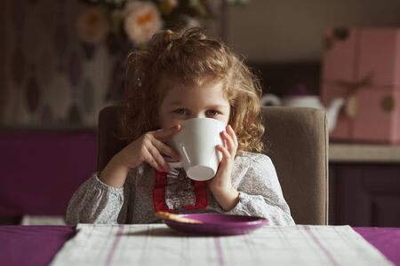 child charming: Little cute girl drinking from a white cup Stock Photo