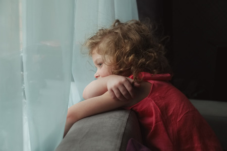 sad cute baby: Little girl waiting for someone and looking out the window Stock Photo