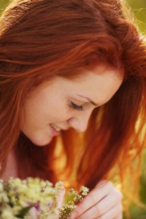 freckled: Freckled red-haired girl with a bouquet of flowers