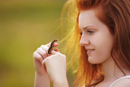 naturalist: Girl holds big brown caterpillar on her hand