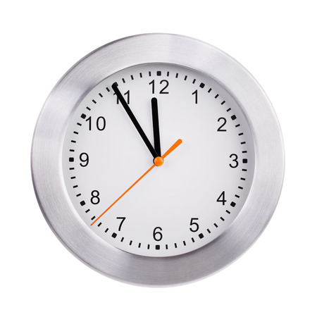 five to twelve: Round office clock shows five minutes to twelve