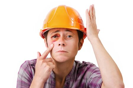 painfully: Female construction worker with a black eye in the helmet