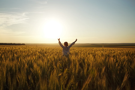 Young woman stands in a field of ripe wheat Stock Photo