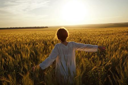 cosecha de trigo: Mujer joven en un campo de trigo maduro