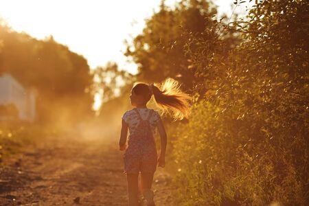 beatitude: Happy girl with long hair running down a country road