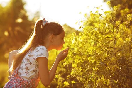 blessedness: Beautiful little girl sniffing a yellow flower