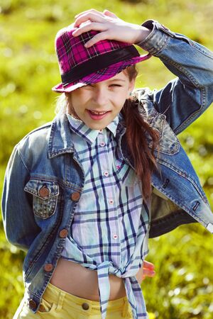 girlie: Happy girl in a denim jacket and hat Stock Photo