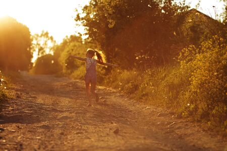 beatitude: Small happy little girl running along a country road
