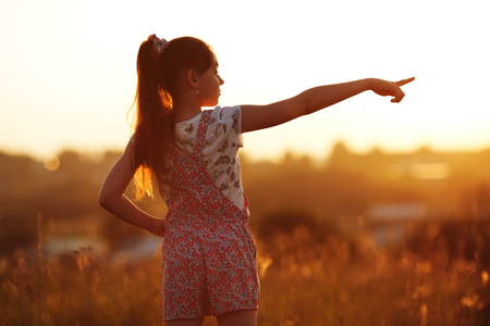 Little girl in a field shows a finger into the distance