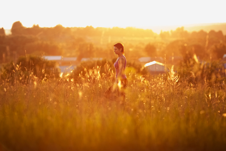 blessedness: Happy young woman walking on the field