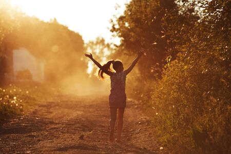 blessedness: Happy girl running on a dusty road in the summer