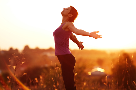 blessedness: Happy young woman with arms outstretched in the field