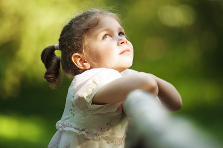 blessedness: Little happy beautiful girl standing and looking up Stock Photo