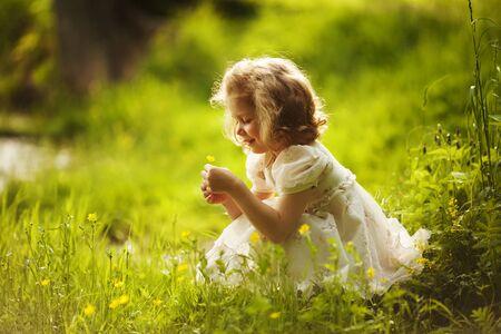 jardines con flores: Niña feliz con una flor en sus manos