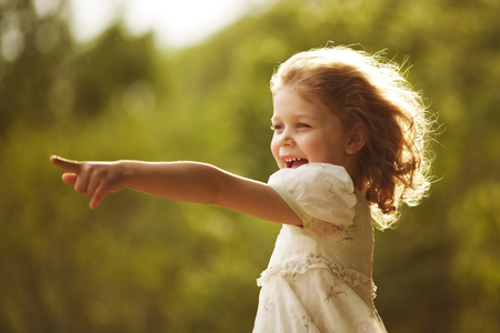 blessedness: Happy curly girl shows a hand somewhere ahead
