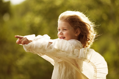 blessedness: Happy girl in dress developing in the wind Stock Photo