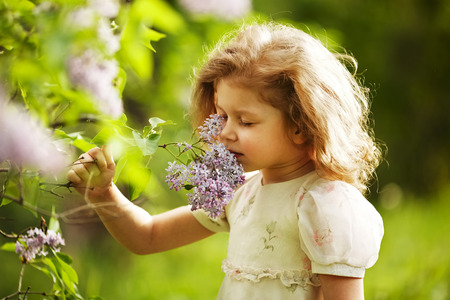 beatitude: little girl inhales the aroma of lilacs
