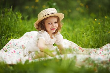 blessedness: Little happy girl is sitting and resting on the grass