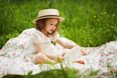 blessedness: Little girl sitting and reading a book Stock Photo