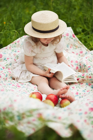 blessedness: Little girl sitting on the grass and reading a book Stock Photo