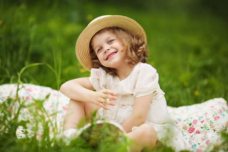 blessedness: Happy girl sitting on the grass and holding a glass of water