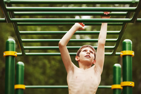 stubbornness: Teen exercise on the playground in summer Stock Photo