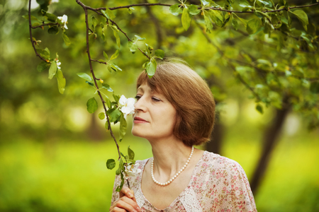 blessedness: Happy elderly woman inhales aroma of a flower