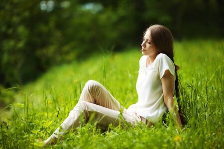 luxuriate: Young pensive woman sitting on the grass Stock Photo