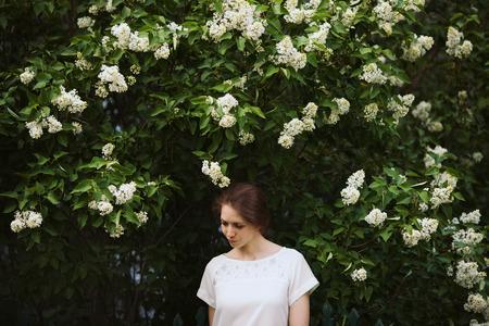 beatitude: Beautiful woman standing next to a bush of white lilac