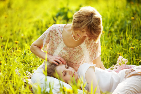 blessedness: Happy mother pats on the head with a sleeping daughter Stock Photo