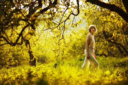 blessedness: Slim woman walking in summer apple orchard