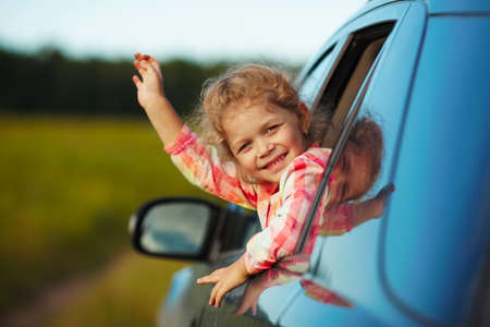 adorable child: Happy litle cheerful girl waving from the car