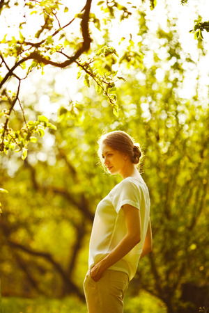 pacification: Beautiful happy girl standing in the summer garden Stock Photo