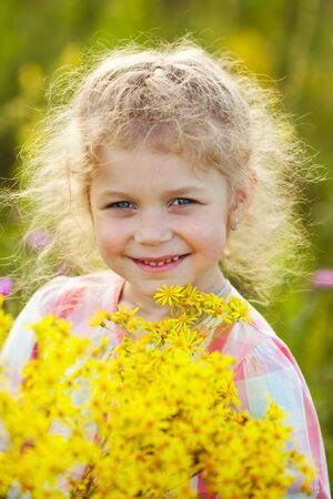 yellow wildflowers: Happy curly-haired little girl with yellow wildflowers