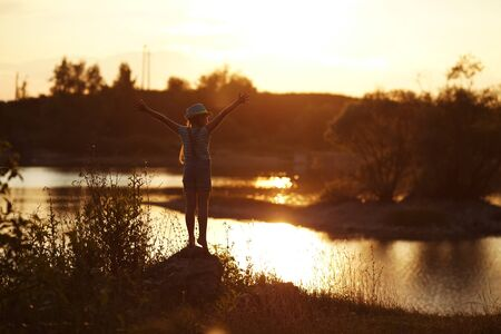 blessedness: Girl stands on the river bank at sunset