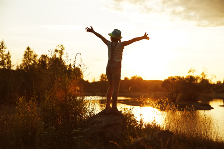 blessedness: Happy girl standing on a rock in the evening