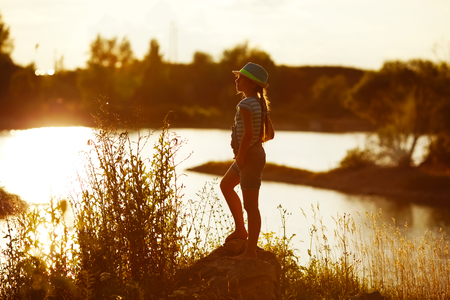 blessedness: Girl in hat stands on the river bank at sunset