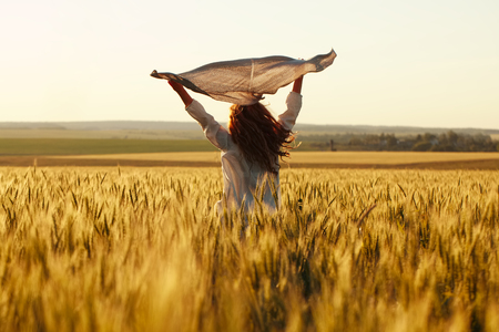 blessedness: Happy woman with a scarf in the evening field