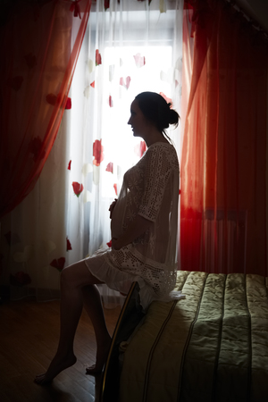 conceiving: Young pregnant woman sitting on the headboard