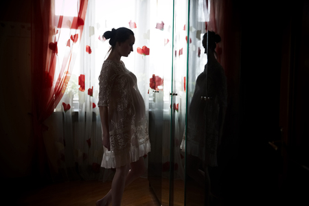 conceiving: Pregnant woman standing in front of a mirror Stock Photo