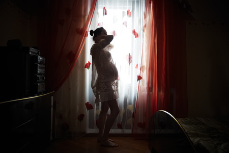 enceinte: Happy young pregnant woman standing in the room Stock Photo