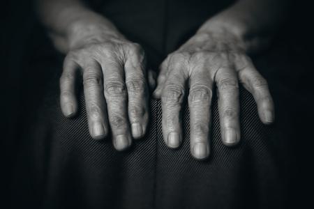 Two hands wrinkled old man on a dark background 版權商用圖片